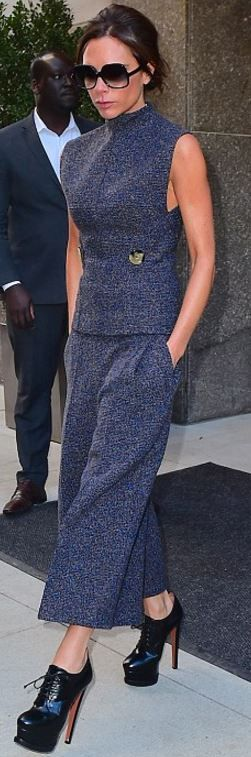 Who made  Victoria Beckham's black platform boots, gray pants, black sunglasses, and button top?