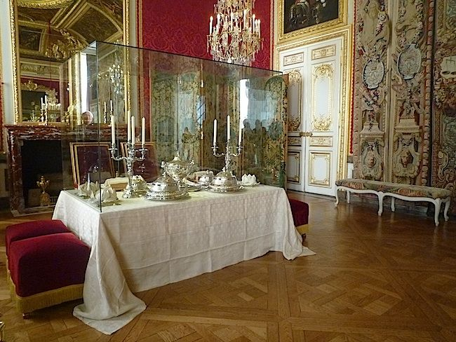 The Salon of the Grand Couvert is part of the Queen's Grand Apartment. Couvert means place setting in French, and this is the room where the royal couple had dinner. The King and Queen sat on armchairs, facing the audience. Duchesses had the privilege of sitting on a row of stools arranged in a semi-circle a few feet in front of the table. Further away stoo the rest of the courtiers and the public, for anyone decently dressed was admitted to the palace.