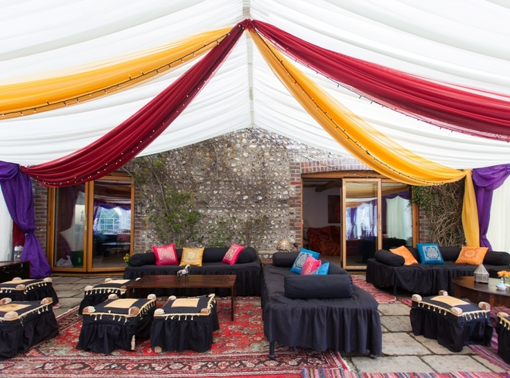 This marquee has been decorated by The Complete Chillout Company. Vibrant, bright draping with fairy lights have been used for the ceiling and walls. Furniture and rugs have also be hired to complete the finish. Perfect for venue decoration. www.completechillout.com