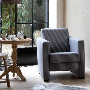 Mix de strakke lijnen van de fauteuil Jens met een zacht kleed en oude materialen. Zo vormt zich een persoonlijk geheel met spannende contrasten.