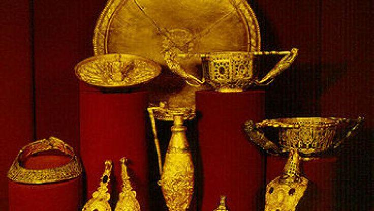 """Povestea Tezaurului """"Cloșca cu puii de aur"""" începe în localitatea Pietroasele, locul în care a fost descoperit din întâmplare de doi țărani în anul 1837. Descoperirea tezaurului de la Pietroasele a declanșat la vremea respectivă o adevărată isterie a căutătorilor de comori."""