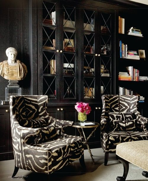 Black sitting area with fantastic zebra print chairs and spellbinding bookcases.
