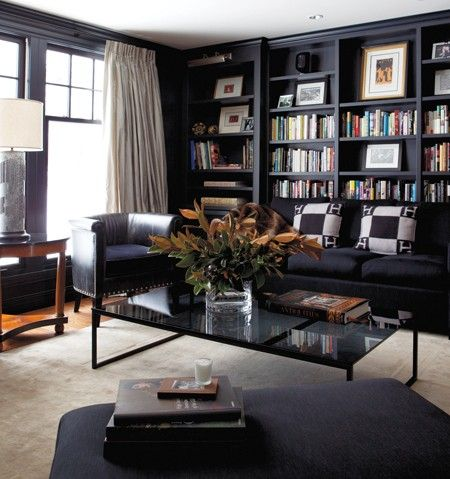 """Dark & Masculine Den Use black bookcases to create an ultra-cosy hangout. Designer Scott Yetman and his partner, Jean Michel Lavoie, call this Ralph Lauren–inspired room — in their Knowlton, Quebec weekend retreat — their """"winter room."""" Scott designed the sofa and had it covered in a nubby charcoal linen. The chair is upholstered in distressed leather with a mohair seat."""