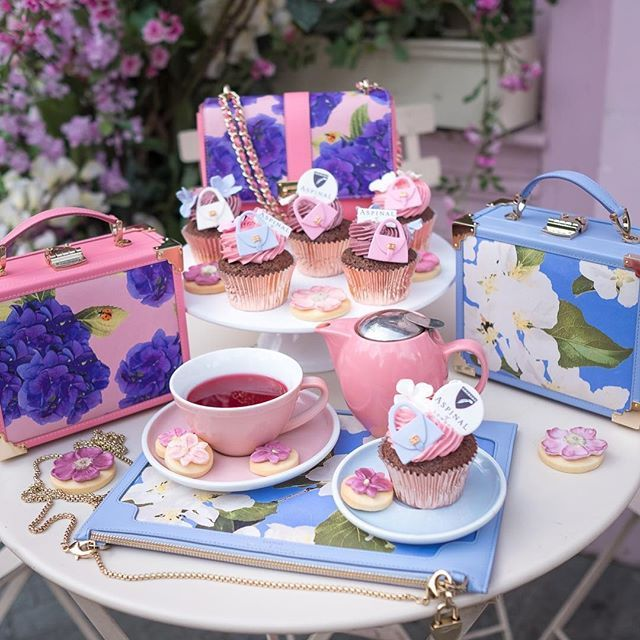 In collaboration with @aspinaloflondon we are delighted to announce the arrival of our limited edition Fashionista Summer Menu here at the Peggy Porschen Parlour! Inspired by Aspinals floral handbag collection with @beautiful_soulxx,  we have created a stunning selection of handbag and hydrangea cupcakes. Chose from scrumptious chocolate sponge iced with raspberry & rose or blueberry & violet buttercream, each topped with a pretty pastel handbag and sugar blossom. Order online or enjoy in…