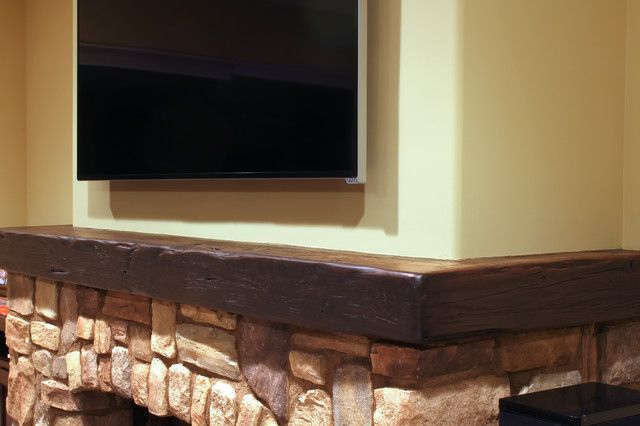 half height stone fireplace ending at wrap around rustic mantle that has slight sheen fireplace