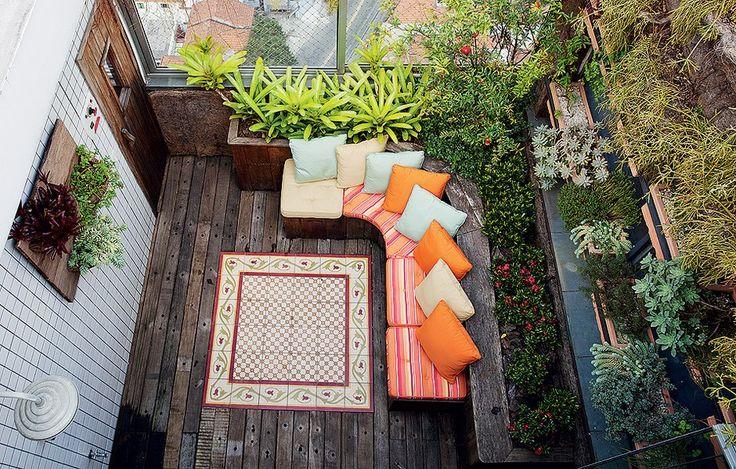 Os moradores queriam um espaço aconchegante e com muitas plantas, em uma varanda de apenas 10 m². A solução da paisagista Susana Udler foi explorar as paredes, com um jardim vertical. Embaixo ficam os bancos-baú, que armazenam ferramentas do jardim. Foto: Revista Casa e Jardim