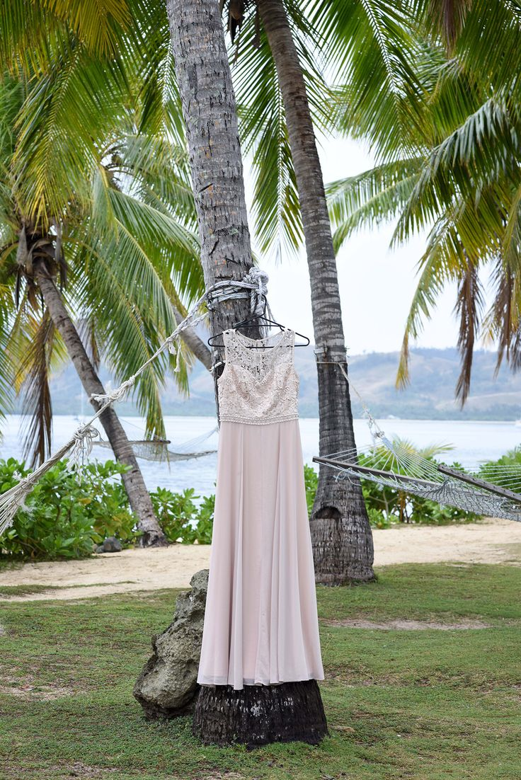 Simple long wedding dress salmon rose pink hanging in front of Fiji palm tree by the ocean.