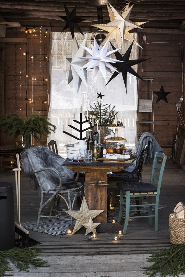Outdoor Rustic Farm Christmas Decor Table Setting with Glowing Star Lanterns and Cute Blue Chairs.