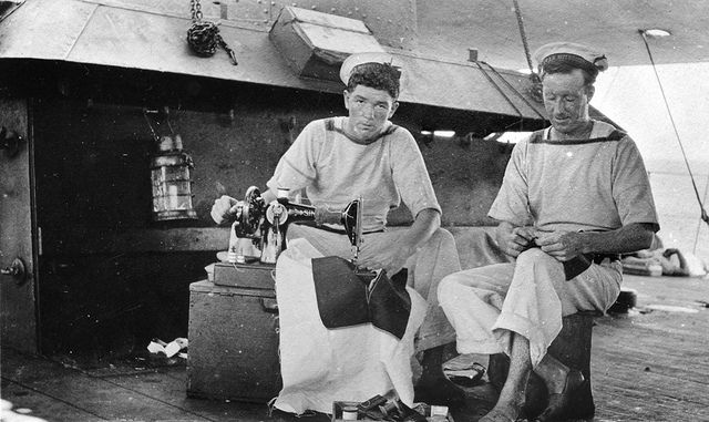 Two signalmen of HMAS Melbourne mend their clothing at sea. 1873 Signalman Ernesto Campagnolo, born in Walhalla, Vic, (left) was lost at sea on 21 December 1916 during some rough weather.  ID number: EN0160 Photographer: Unknown Place made: North Sea, Atlantic Ocean Date made: 1916. No known copyright restrictions. This photograph is from the Australian War Memorial's collection www.awm.gov.au Persistent URL: cas.awm.gov.au/item/EN0160