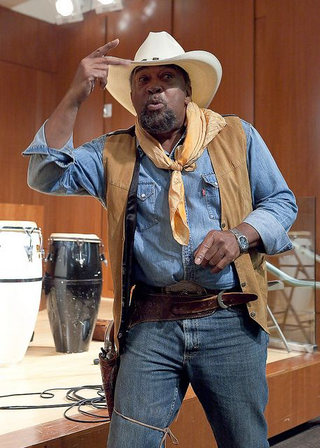 "Izell Glover, Black Cowboy, is a storyteller, teacher, artist, and cowboy. A founder of the Black Cowboys, he tells historical legends of Black cowboys such as ""Legend of Nat Love, Annie Oakley and Wild Bill Hickock."" He has been teaching at Medger Evers College in 1989 as an adjunct and became a fulltime professor (in the Department of Mass Communications) in 1995. For over 50 years, art has been an indispensable aspect of his existence..."