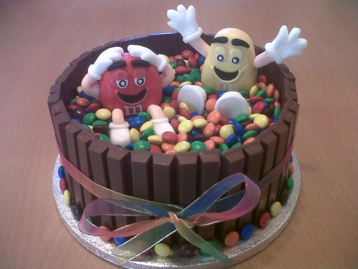 This is an m chocolate birthday cake made with a chocolate madeira sponge with kit kats around the outside. Also I have made the m figures by hand using fondant and added m's to fill in the middle section of thee cake. Also a rainbow bow was added for a bit of extra decoration.