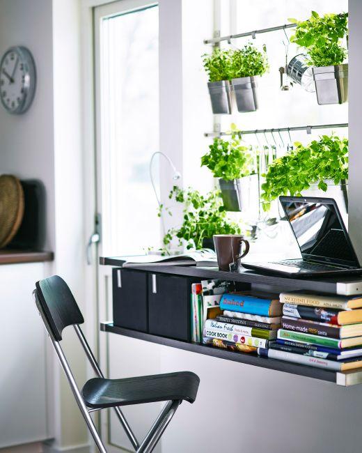 Två hyllor framför en fönsterbräda. En används som skrivbord där det står en bärbar dator. På den andra hyllan förvaras böcker.