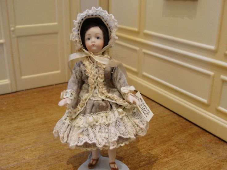London Supply Company - porcelain little girl  costumed in a beautiful antique style dress with lots of beige lace. She wears white lace-trimmed pantaloons and petticoat. She has long brown hair with a beige bow in the back. She wears a gorgeous matching bonnet trimmed with rosettes and lace.  sold on ebay for $119