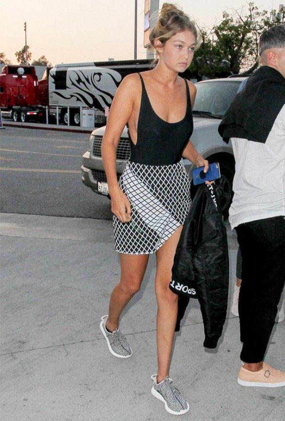 Gigi Hadid wears a black bodysuit, printed skirt, and Yeezy Boost sneakers