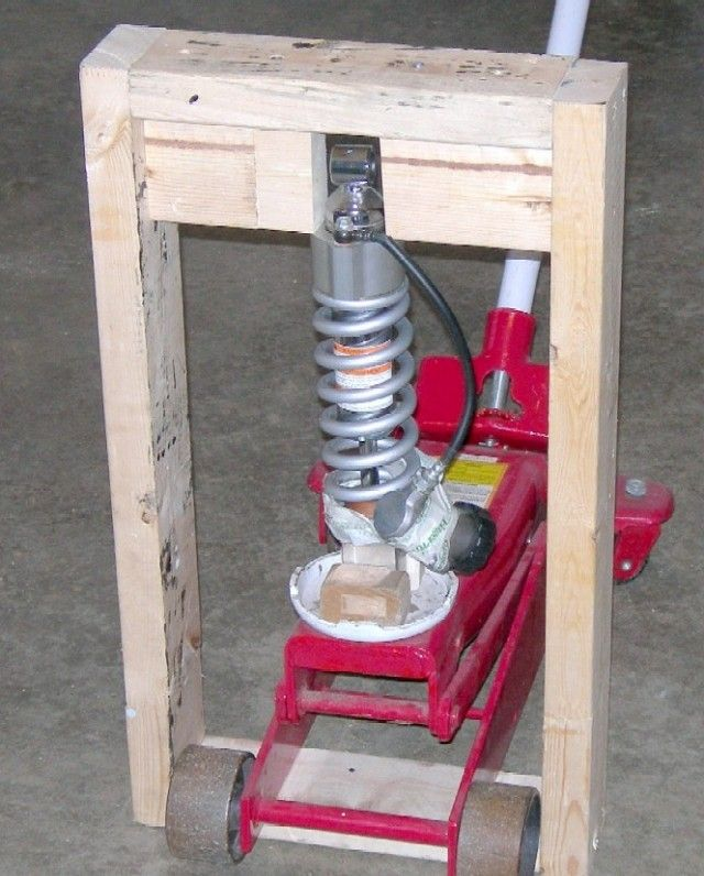 Shock Spring Compressor by Isle Rider -- Homemade shock spring compressor constructed from 2x4s and intended to facilitate the process of removing the snap-ring from a motorcycle shock absorber. Utilizes a floor jack to apply the necessary force. http://www.homemadetools.net/homemade-shock-spring-compressor
