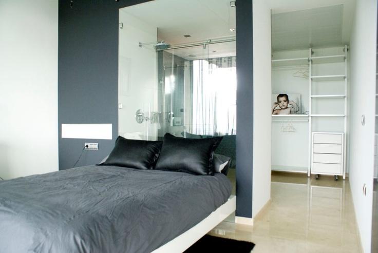 habitación con baño totalmente integrado, el espacio de ducha acristalado sirve de elemento separador entre ambos