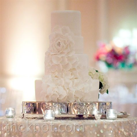 Feminine sugar flower petals cascaded down the four-tiered, round fondant cake.