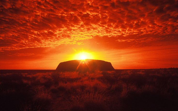 The sky is set on fire by this gorgeous sunset behind Ayres Rock in Uluru, Australia
