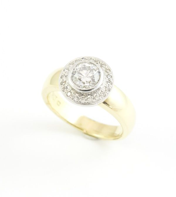 18ct yellow gold engagement ring with central diamond in halo setting.  http://www.designworksstudio.ie/shop/18ct-yellow-gold-engagement-ring-with-central-diamond-in-halo-setting/