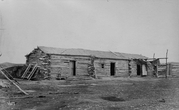 Black and white photograph of a long, single-storey log home with several doors, and tools and implements surrounding the building