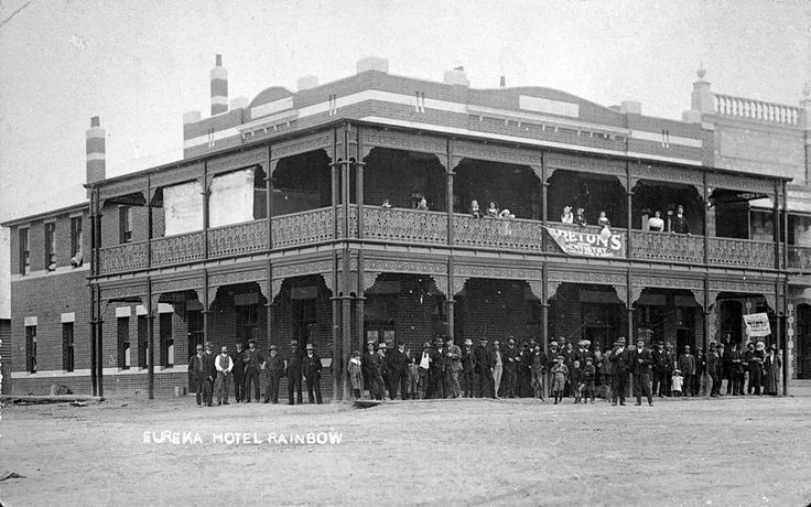 A crowd outside the Eureka Hotel in Rainbow. A banner on the balcony advertises Breton 's Dentistry, 1912.