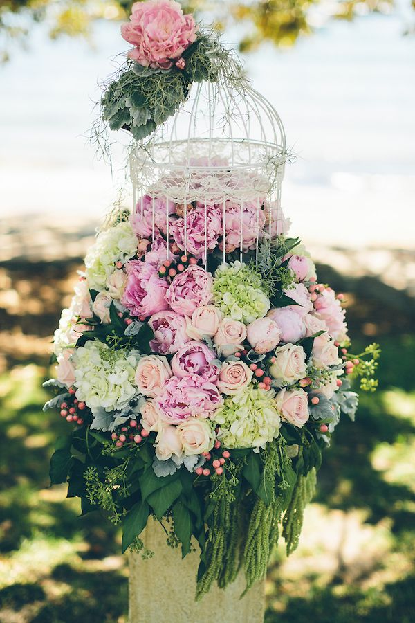 Wedding plinth with a birdcage adorned with flowers at the end of the ceremony aisle beneath the Dunbar House fig tree.