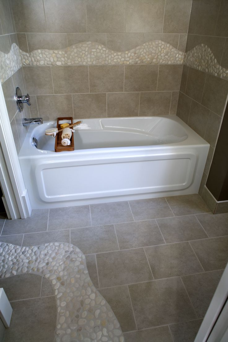 A contemporary style bathroom covered in porcelain tile and river rock detailing. This is a great example of how to spruce up a white bathtub. See all of the 2016 bathroom remodeling trends by clicking on the pin.
