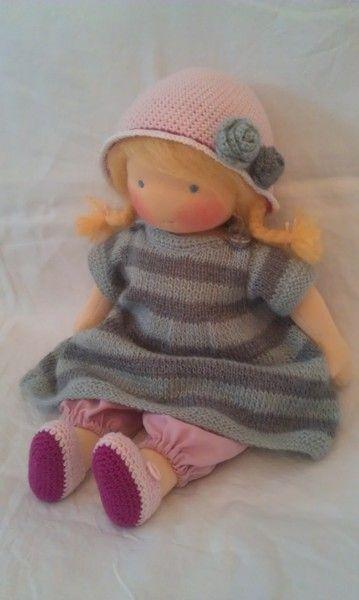 Luzie hat hellblaue Augen und goldblonde Haare aus Puppenmohair, die zu Zöpfen geflochten sind.  Sie trägt ein Strickkleid aus flauschigem Mohair...