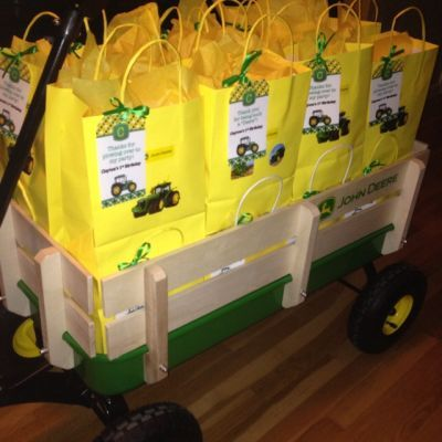 John Deere birthday party favors presented in a wagon filled with bright yellow bags trimmed with John Deere green.  See more John Deere birthday party ideas at www.one-stop-party-ideas.com