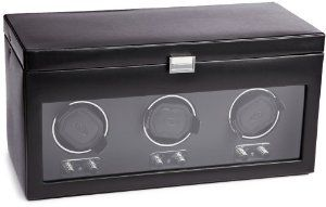 """Wolf Designs 270502 Heritage Module 2.1 Triple Watch Winder with Cover and Storage Wolf Designs. $599.00. Black faux leather exterior, chrome clasp closure and control turn knobs with tempered glass cover. Newly designed watch cuff to fit larger, heavier watches. Dimensions: 17.25""""w x 7.75""""d x 8.75""""h. Patented rotation program: intermittent rotation with pause and sleep phases pre-programmed. Operates on 3.3V adapter (included) or D-Cell alkaline or lithium batteries."""