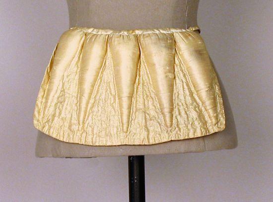 1828-55, Pokissen bzw. sehr frühe Tournürenform zur Betonung des Hinterns mit karottenförmigen Austopfungen, aus Seide und Baumwolle, gehalten durch ein Seidenband, vermutlich USA