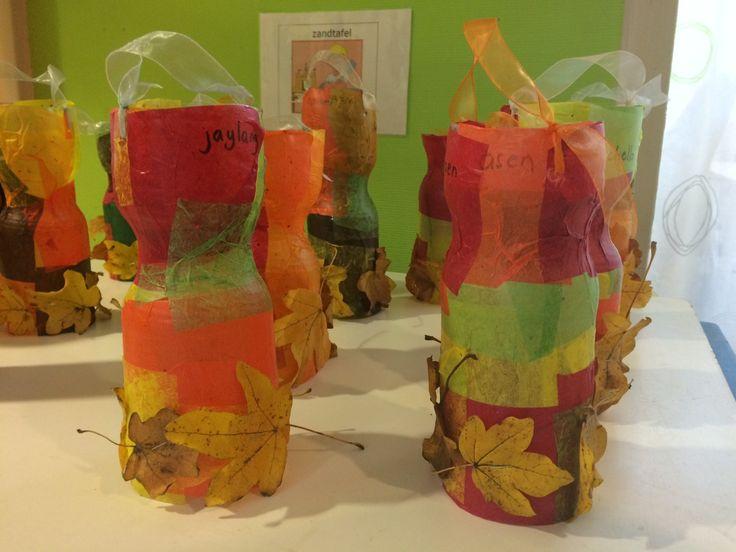 Frisdrank flessen boven en onderkant knippen, beplakken met vliegerpapier met lijm smeren en bladeren eraan nieten.