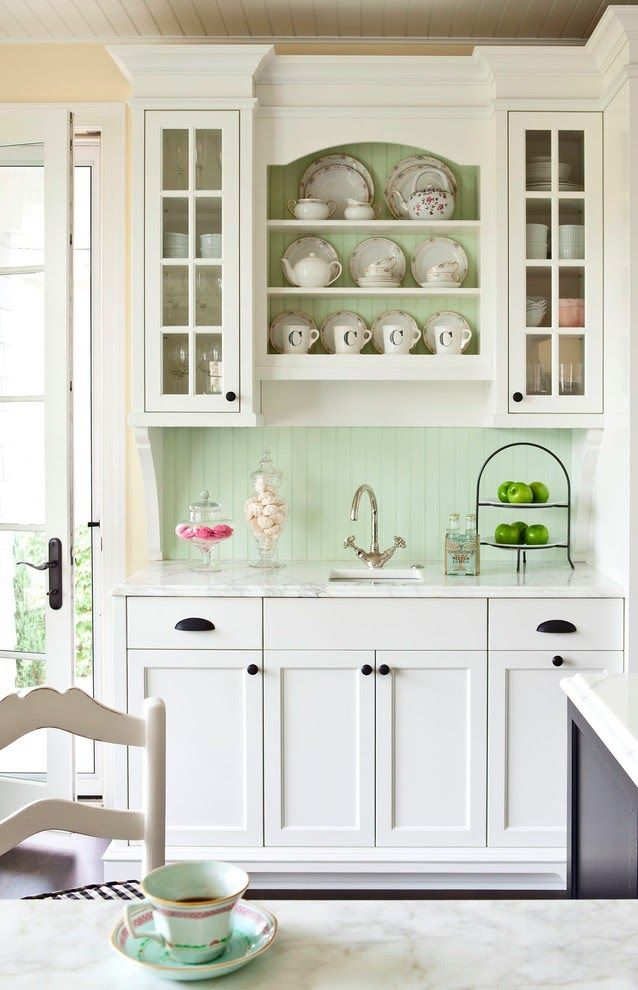 French country Kitchen. Mint green paint wall color / backsplash. White cabinets, shelves. Marble countertop. Black hardware, handles.