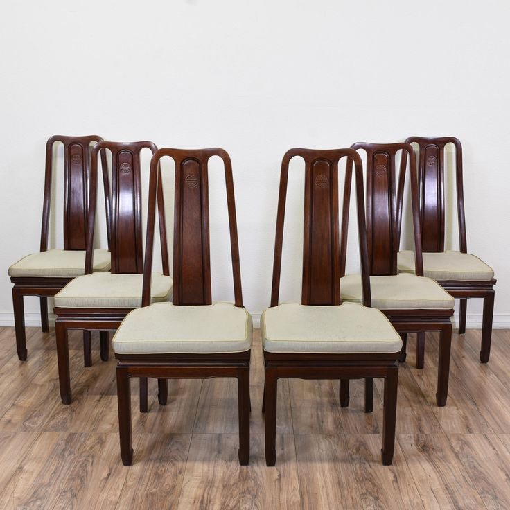 These Asian dining chairs are featured in a solid wood with a cherry finish. Each side chair has a grey squab cushion, carved apron, and an intricate design on its splat. Perfect for adding a touch of elegance to the dining room! #asian #chairs #diningchair #sandiegovintage #vintagefurniture