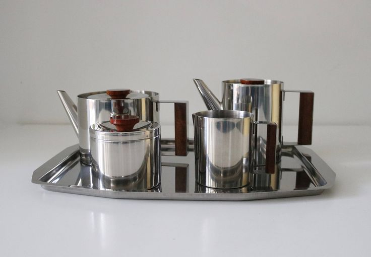 Modernist styling, clean lines and rich contrasts: this teak and stainless steel set comprises 2 pots (coffee/water/tea) a milk jug, sugar bowl and tray. In lovely condition with no dents and just light surface wear. Some variation in the wood colour on lids and handles (water jug is quite dark).
