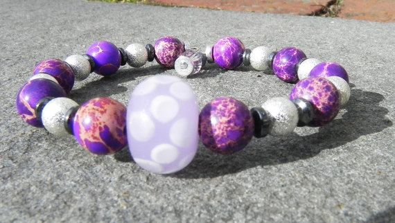 """This bracelet features Imperial Jasper stone, silver plate and center glass bead on memory wire. Bracelethas beaded charms on ends. This bracelet looks great worn alone or paired with others. * All jewelry is handmade in my studio.  * Bracelets are on average sized to 7"""" average wrist. Please contact me and accommodations can be made if your size is above or below that range.  * Processing time is 1-2 days.  * US orders are shipped first class mail. Thank you for visiting my shop"""