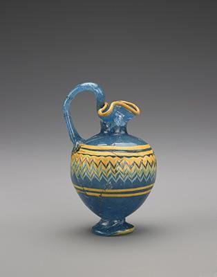 Description: Phoenician Oinoichoe Material(s): Glass Date of Object: 400-350 BC Origin: Rhodian Measurements(s): H: 11cm, D: 6cm, D of foot: 3.3cm, Weight: 109.1g Provenance: The Georgian National Museum Find Location: Vani, Grave 6