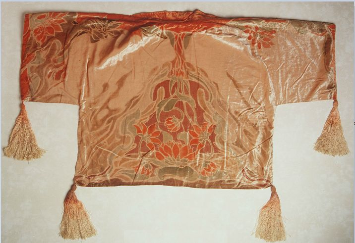 Cape, evening, women's, beige velvet with orange hand painted design of water lilies, Lucy Dalgarno (1874-1945)  1930 She was a prolific artist and designer, with a passion for brilliant colour. She created many new techniques in her work that reflected the ideals of the Arts and Crafts movement of the late 19th century. In her studio shop in Victoria Arcade near Rowe Street in Sydney she designed bridge capes like this one.