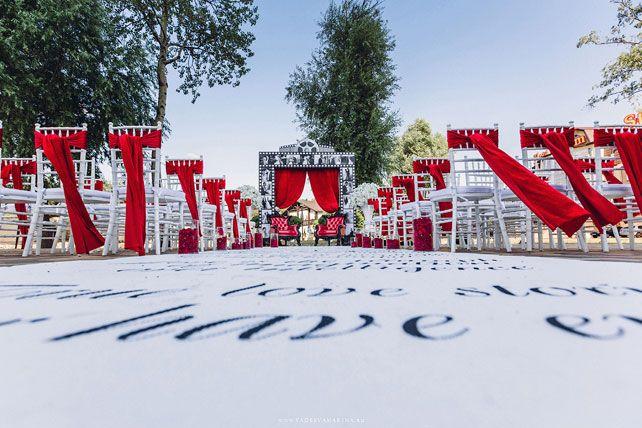 Свадьба в стиле Голливуд, место церемонии, красные банты на стульях, арка в виде киноленты