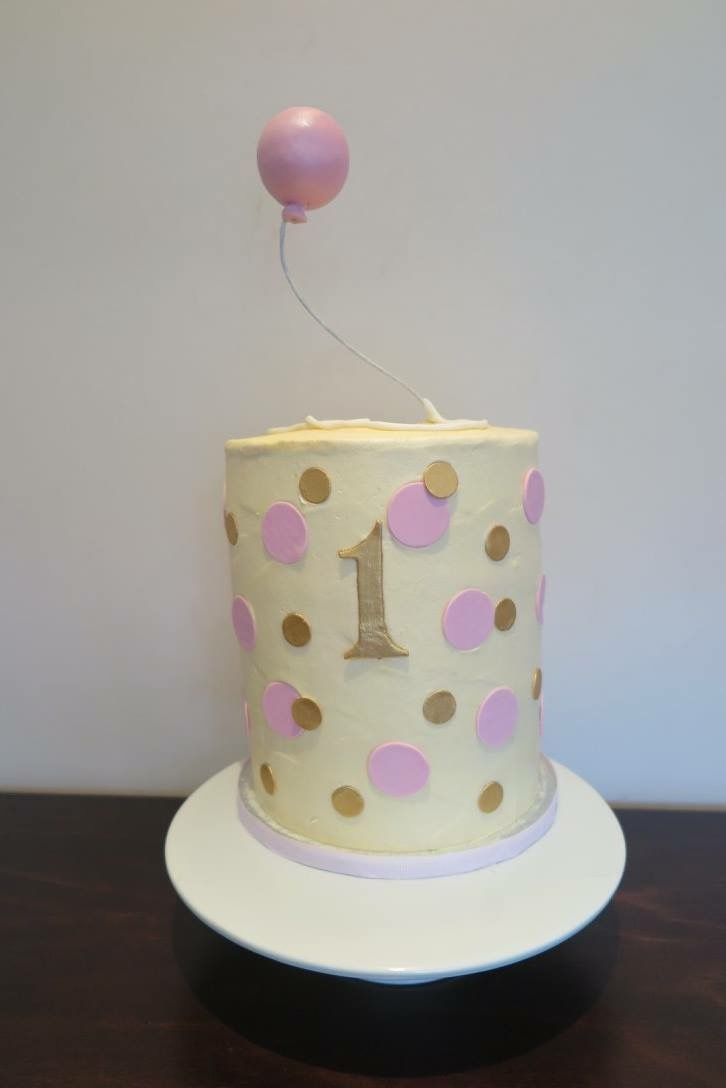Pink balloon cake with gold and pink spots.