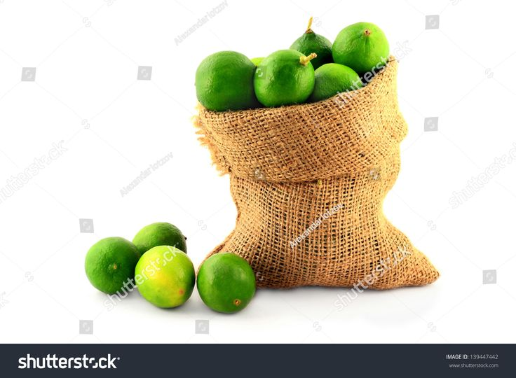 Fresh Citrus Fruits Organic Key Limes in Burlap Bag and spilled around over white background.
