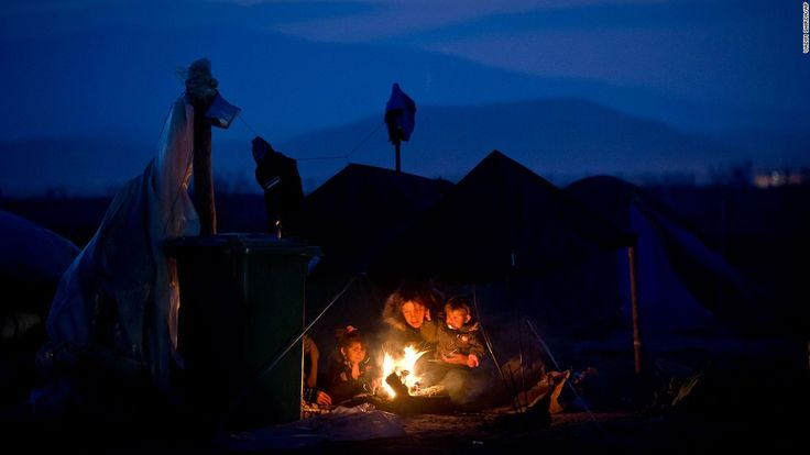 A woman sits with children around a fire at the northern Greek border point of Idomeni on Saturday, March 19.