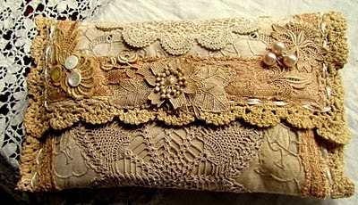 Little purse created from vintage doilies,dyed lace, pearl thread and pearl buttons...By:suziqusthreadworks