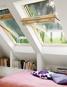 Attic bedroom with bookcases and skylights