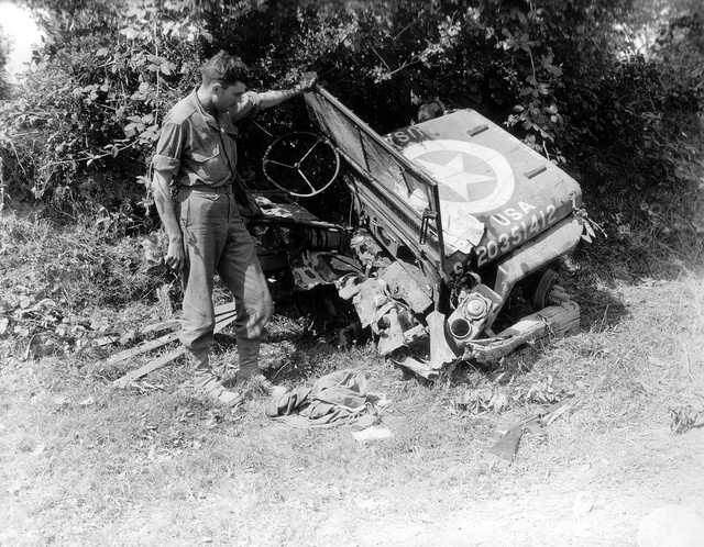 A U.S. soldier inspects an American Jeep bisected by a mine. Photo taken August 4, 1944 on the road to Saint Sever. France.