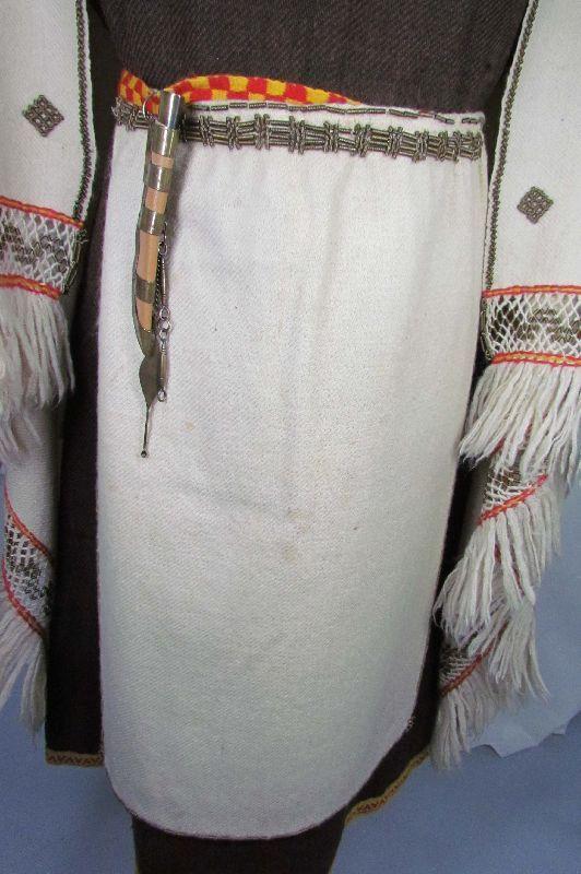 Perniö Esiliina  väri valkoinen jota koristaa vyötärölle kiinnitetty spiraalikoriste .Vyönauhoina on kelta-punaiset lautanauhat.