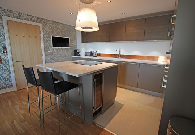 The open plan kitchen and living room arrangement had left a significant amount of unused space, and this was perfect for introducing this Beige grey satin lacquer kitchen island with breakfast bar.