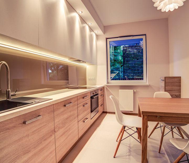 Nowoczesne wykończenie kuchni o układzie liniowym. Drewniane i białe fronty szafek. Oświetlenie LED i halogenowe w kuchni.