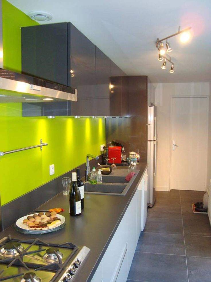 Modern and arty kitchen with a lime green splashback and wall and grey bench tops. APRES TRAVAUX by acctif design