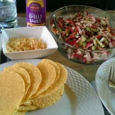 - Verwarm je taco schelpen - Snij een halve komkommer en 2 grote tomaten in reepjes - Voeg 250 gram gerookte kipreepjes toe - Snij 5 radijsjes in reepjes - Voeg een blikje Mexicano maïs toe (zonder vocht) -Voeg de kruiden toe naar smaak Alles mengen en opdienen in schaal. - Rasp de kaas (indien nodig) Vul je taco met wat peperkaas, wat chilisaus en de vulling die je net gemaakt hebt.